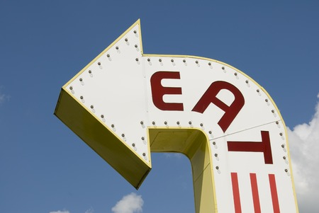 caf: A three-dimensional metal EAT sign in a sans-serif typeface.
