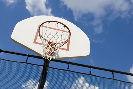 A basketball hoop in a childrens playground stands against a partly cloudy blue sky. photo