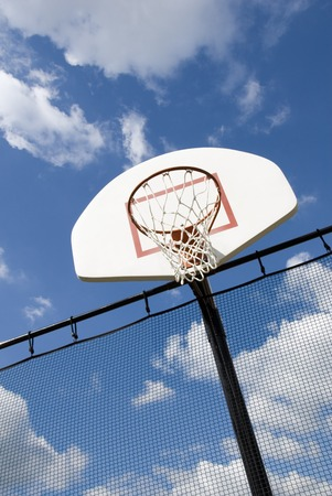 A basketball hoop in a children's playground stands against a partly cloudy blue sky. Stock Photo - 1566276