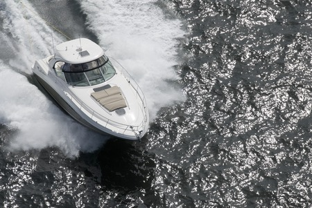 A white and tan speedboat shot from above while travelling fast. Stock Photo