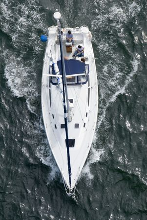 A luxury yacht shot from above as it motors out to sea. Stock Photo