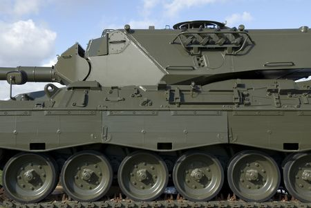 invincible: A detail of a European-built main battle tank against a partly cloudy sky.