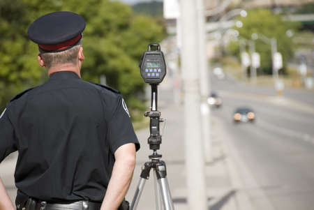 A North American policeman waits to catch speeding drivers with a radar gun. (Shot with minimum depth of field. Focus is on the police officer and radar gun.)