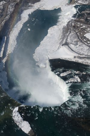 horseshoe falls: An aerial shot of the Canadian and American sections of Niagara Falls, with snow still present in early spring. The rainbow on the left of the frame was created by light refracted through the mist rising from Horseshoe Falls.