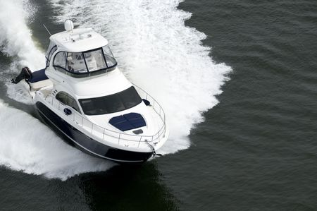 speedboat: A blue and white speedboat shot from above while travelling fast.
