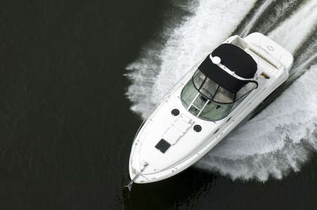 speed boat: A black and white speedboat shot from above while travelling fast.