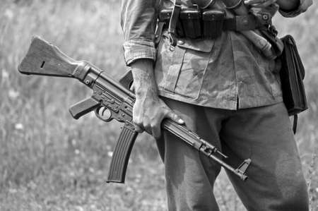 one armed: A world war two German soldier holding an MP43 submachine gun. Shot with minimum depth of field. Focus is on the hand and gun.