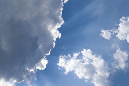 radiating: Che irradia la luce del sole attraverso le banche cumulo di nuvole.  Archivio Fotografico