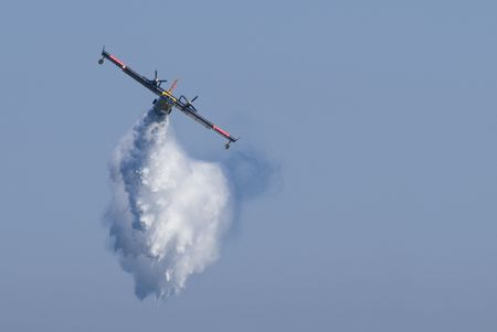 dumping: A twin-engined  bomber dumping its load on a forest fire.
