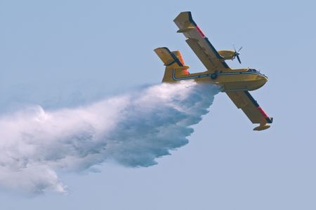 quell: A twin-engined  bomber dumping its load on a forest fire.