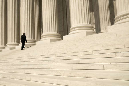 government: A man ascending the steps at the entrance to the US Supreme Court in Washington, DC.