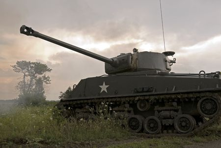 drab: A WWII mark IV Sherman tank moving through hostile terrain during a thunderstorm. Its main gun has just been fired and the smoke is still visible in front of the tree.