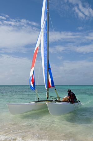 hobie: A small catamaran rapidly approaching a Caribbean beach. Stock Photo