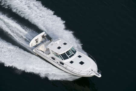 A white speedboat shot from above while travelling fast.