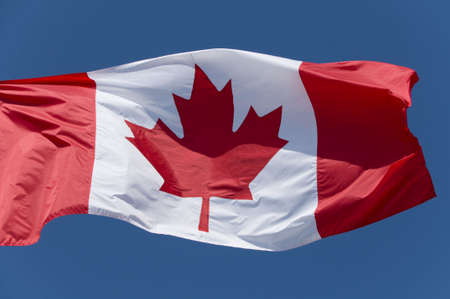 The Canadian flag flying against a bright blue sky. Stock Photo