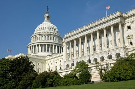 The US Capitol Building where the House of Representatives is in session under the flag flying on the right. photo