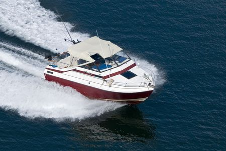 motorboats: A red runabout shot from above while travelling fast.