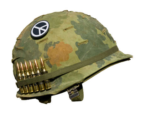 A US military helmet with an M1 Mitchell pattern camouflage cover from the Vietnam war, with six rounds of 7.62mm ammunition and a peace symbol button. Stock Photo