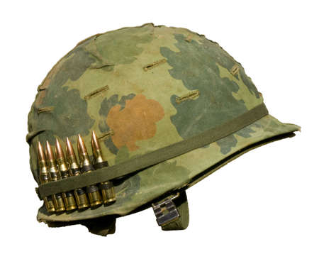 war and military: A US military helmet with an M1 Mitchell pattern camouflage cover from the Vietnam war, and six rounds of 7.62mm ammunition.