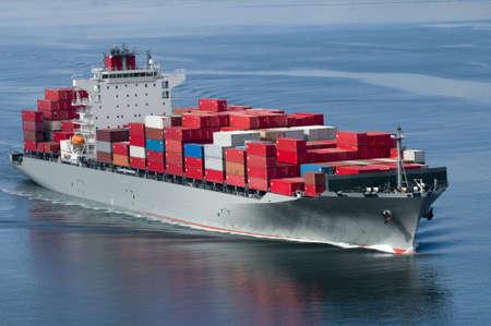 freight container: Un barco de contenedores que llegan a puerto en un d�a muy tranquilo.