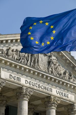 The flag of the EU flying in front of the German Reichstag in Berlin. The phrase Dem Deutschen Volke (To the German people), designed by Peter Behrens, was added to the building in 1916.
