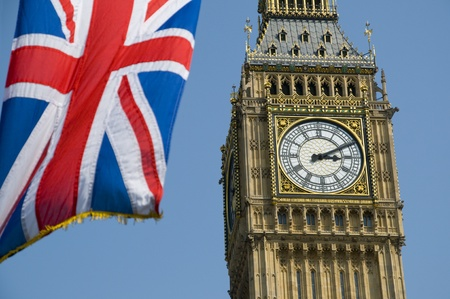 commonly: The Union Flag flying in front of the clock tower, commonly referred to as Big Ben, of the Palace of Westminster.