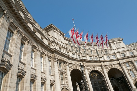 Admiralty Arch in London with eight white ensigns, the flag of the British Royal Navy, flying.