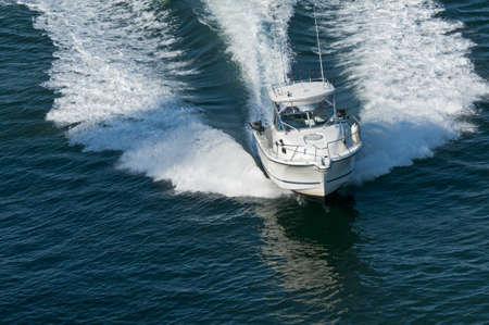 A speedboat moving through calm water in the Pacific Ocean.  photo