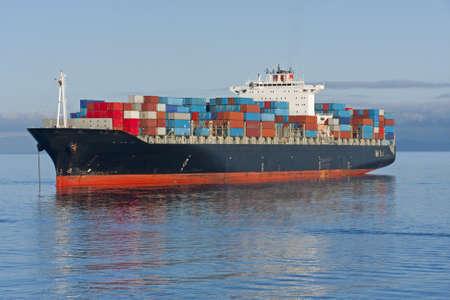 containerschip: Een container schip voor anker in een haven.