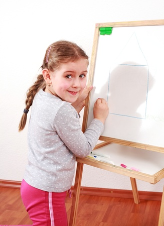 Cute girl painting on chalkboard photo