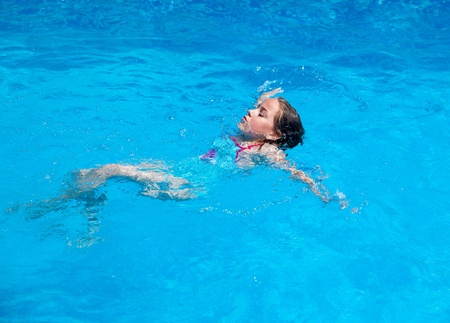 Child swimming backstroke in the swimming pool photo
