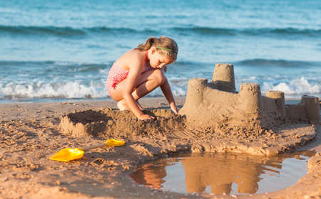 children sandcastle: Relaxed child builds sandcastle on the beach