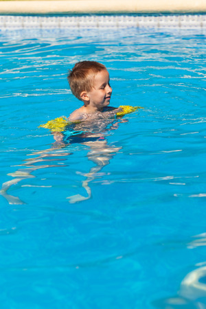 floats: Happy boy swimming with floaties in swimming pool
