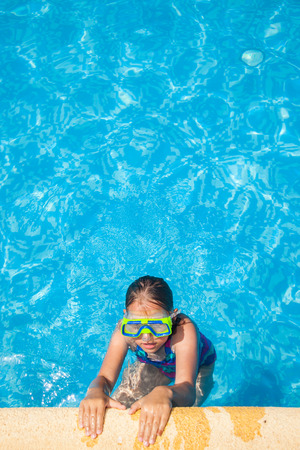 Happy girl with goggles relaxing in swimming pool Stock Photo - 30529437
