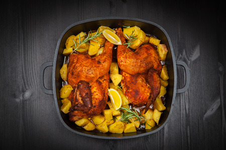 Tasty baked chicken with potatoes and herbs photo