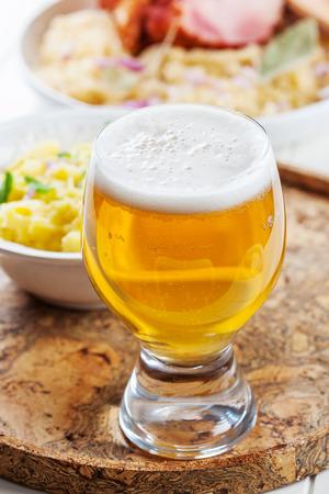 Stil: Mug of beer with dinner in the background
