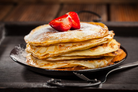 powdered sugar: Pancakes or crepes with fresh strawberries and powdered sugar