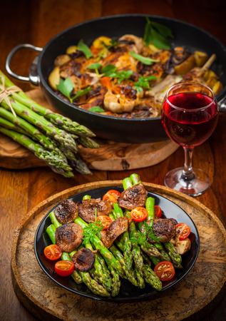 alimentos y bebidas: Ensalada de espárragos verdes con setas asadas y vino tinto Foto de archivo