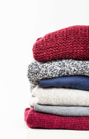 snug: Stack of handmade wool sweaters isolated