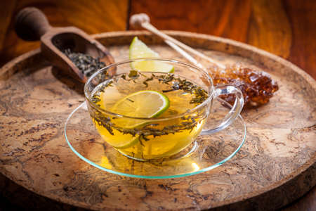 tea spoon: Cup of green tea with dried tea leaves Stock Photo