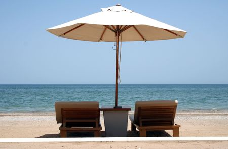 loungers: Sun loungers on a beach underneath a parasol