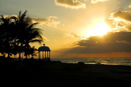 varadero: tropical beach with palm trees and a little chapel at the sunset. Varadero, cuba