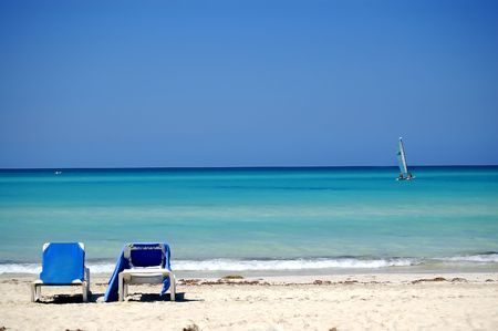 caribbean beach with a recreation sailing boat and two chairs in the first plan  photo