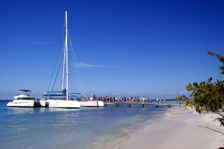 people waiting in a pear for the catamaran, at a desert beach