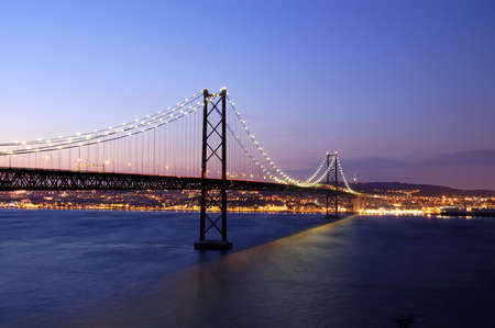 The 25 de Abril Bridge   is a suspension bridge connecting the city of Lisbon, capital of Portugal, to the municipality of Almada on the left bank of the Tagus river. It was inaugurated on August 6, 1966 and a train platform was added in 1999. It is often Stock Photo