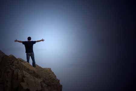man on the top of a cliff with open arms  Stock Photo