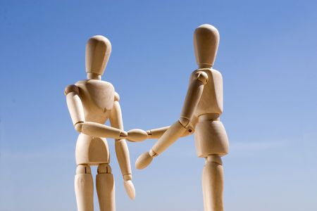 two wood models shaking hands