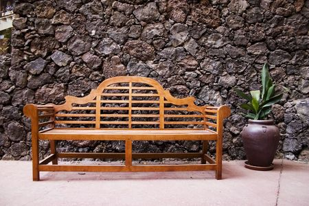 Bench with a stone wall on back photo