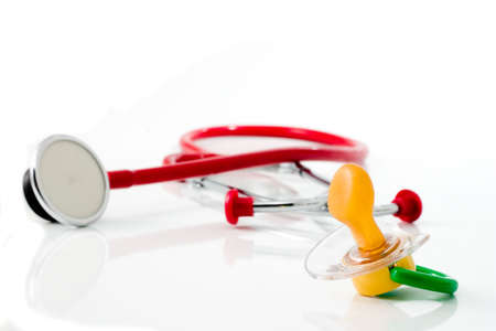 paternity: red stethoscope with green pacifier isolated Stock Photo