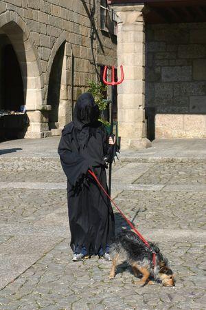 carnival devil costume - devil holding a pitchfork and a dog